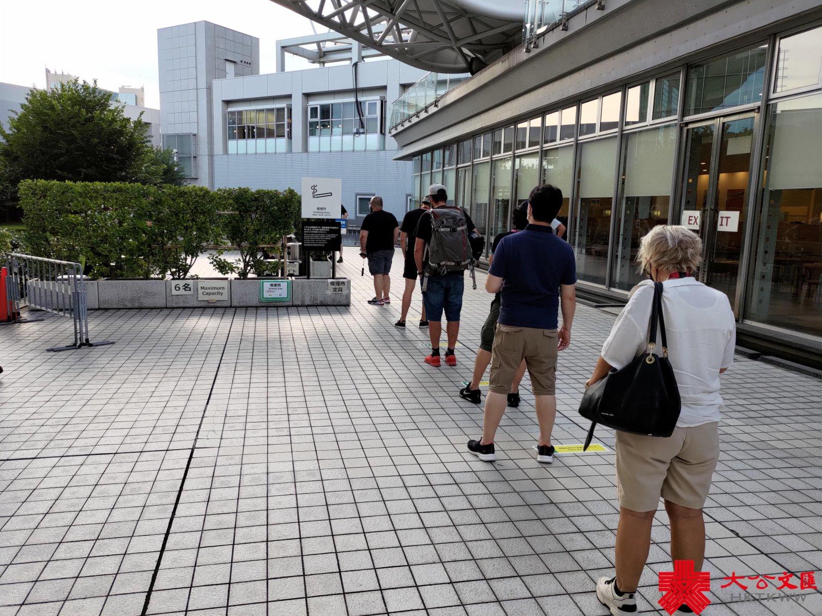 傳媒中心場館外設有專門吸煙區,長期有記者在外排隊。(大公報記者張銳 攝)