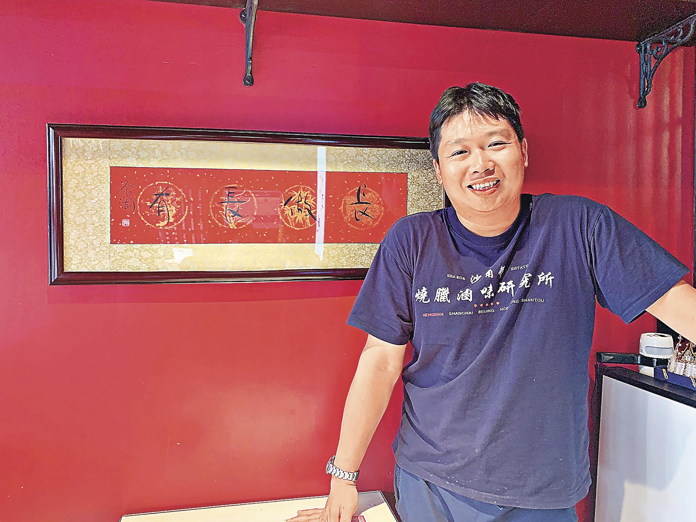 ■蔡志強在新店「燒臘滷味研究所」裏與蔡瀾為他寫下的「長做長有」合影。